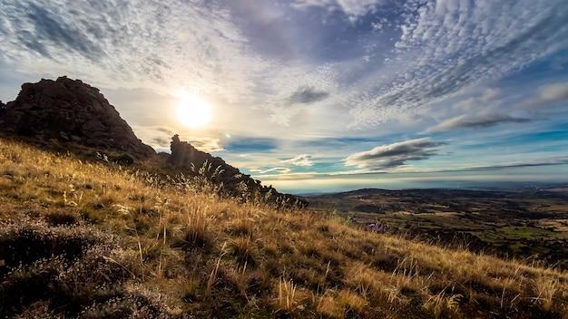 Paisagem dramática de madrid montanha escura com nuvens e sol na frente, pedras e plantas. espanha. cerro san pedro.