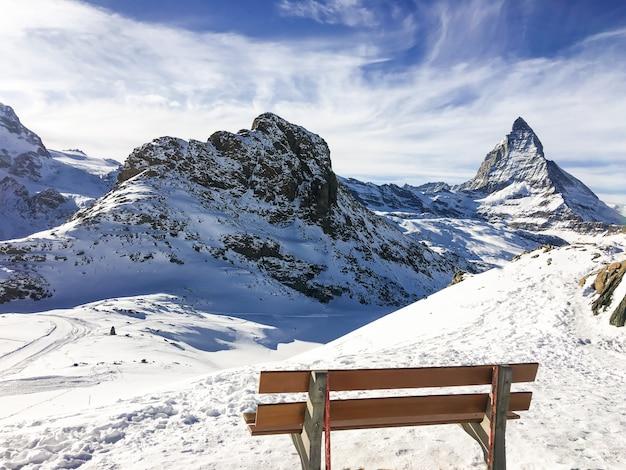 Paisagem e natureza da montanha matterhorn da opinião de madeira da cadeira na manhã com o céu azul em zermatt, suíça.
