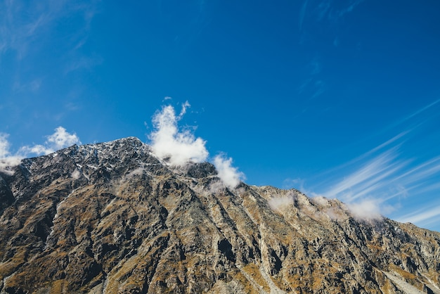 Paisagem ensolarada de outono cênica com alta montanha rochosa com topo pontiagudo em nuvens baixas, sob o céu azul. impressionante vista alpina ao belo pináculo afiado ao sol. pico da bela montanha à luz do sol.