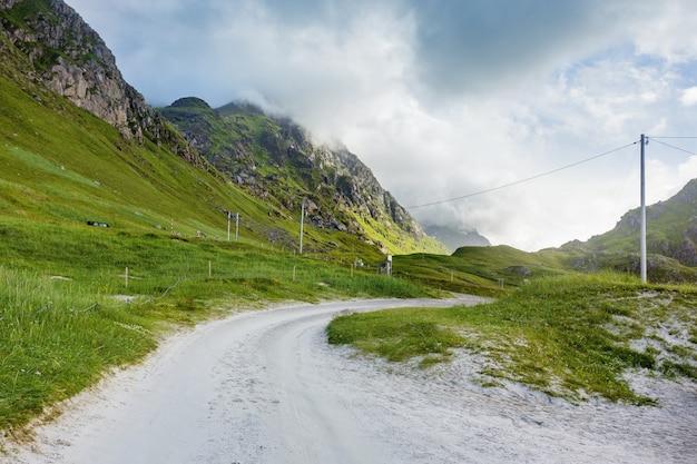 Paisagem escandinava com prados, montanhas e estrada. viagem de carro nas ilhas lofoten, noruega.