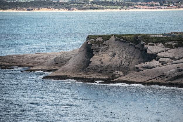 Paisagem espetacular da costa rochosa gramada do mar ondulado sob um céu nublado e cinza em cabo mayor
