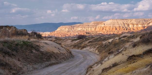 Paisagem fantástica de desfiladeiro e rochas no vale vermelho da capadócia, na turquia, com a estrada