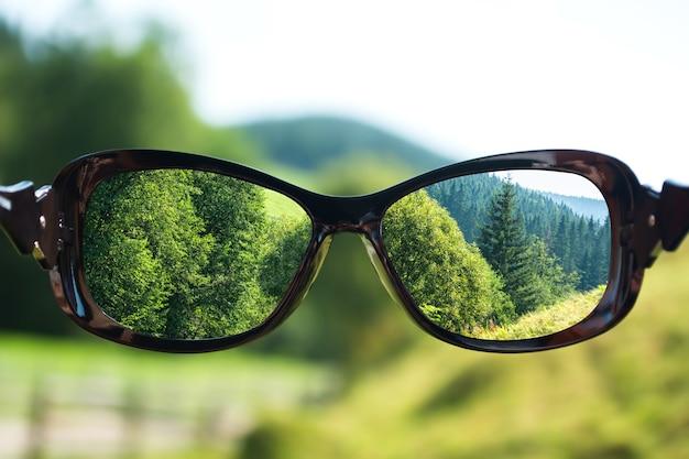 Paisagem focada em lentes de óculos sobre a foto desfocada