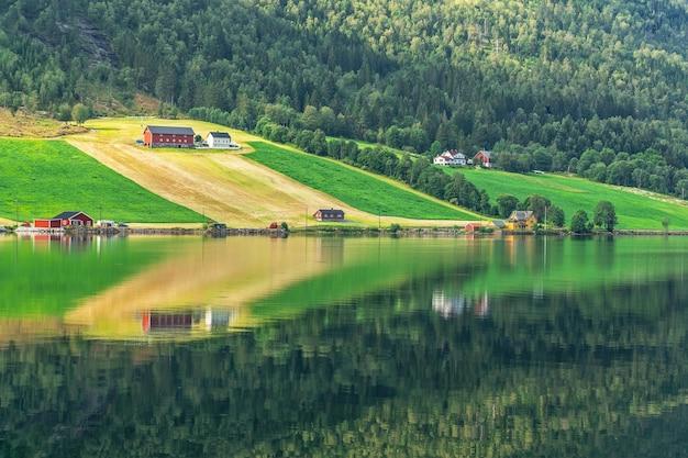Paisagem idílica rural verde com reflexo, casas de aldeia no campo