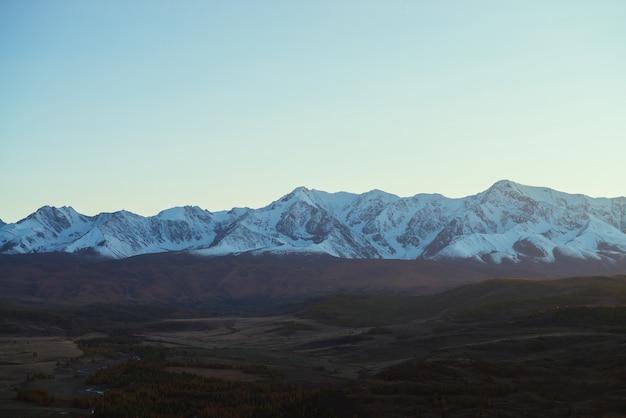 Paisagem incrível com vale montanhoso com colinas e florestas em cores de outono na sombra com vista a grande cordilheira nevada no pôr do sol. altas montanhas cobertas de neve e vale no outono com pouca iluminação