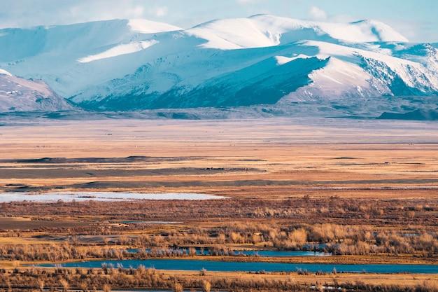Paisagem incrível da área de estepe com lagos e árvores suavemente se transformando em montanhas com picos cobertos de neve. montanhas de altai