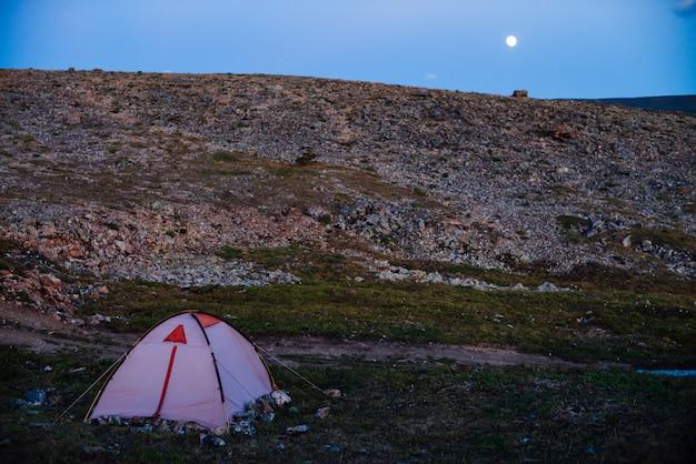 Paisagem incrível do crepúsculo nas montanhas com tenda na passagem em luz violeta