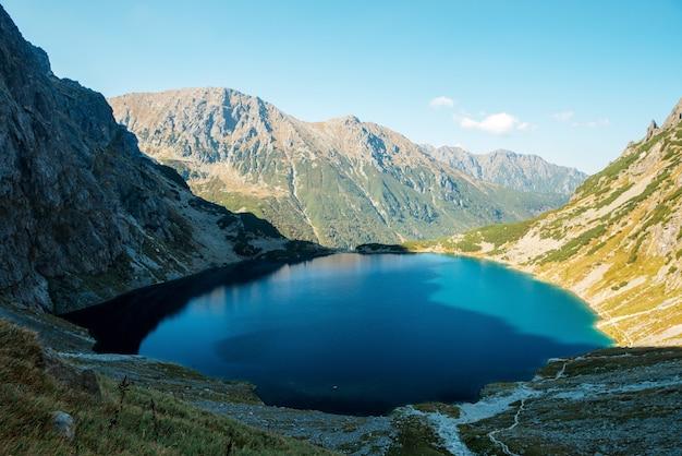 Paisagem incrível do lago morskie oko com água verde cercada por montanhas rochosas