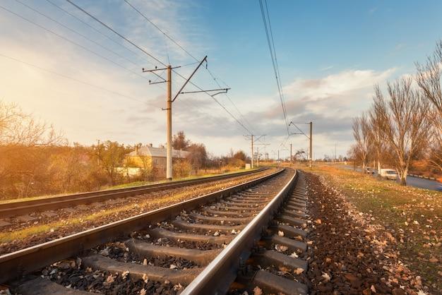 Paisagem industrial com estação ferroviária ao pôr do sol