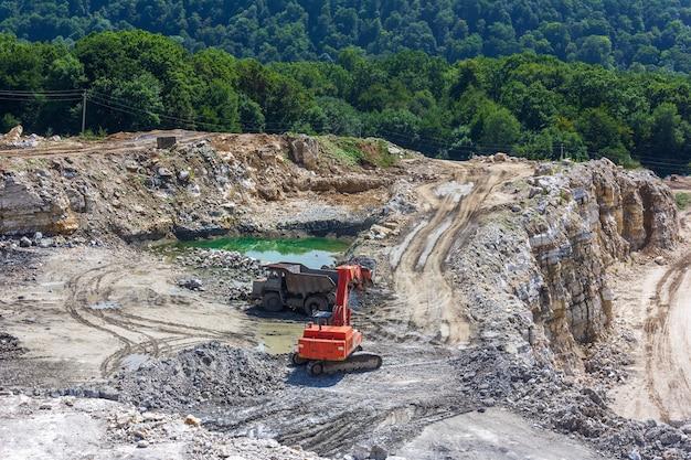 Paisagem industrial com uma escavadeira e um grande caminhão trabalhando em uma pedreira de gesso no verão
