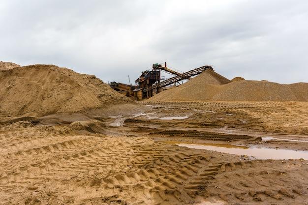 Paisagem industrial deserta com separador gravitacional enferrujado estacionário de areia e cascalho no horizonte