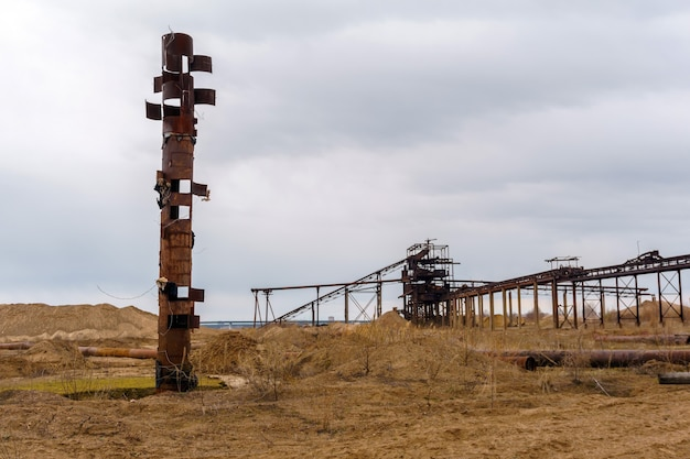 Paisagem industrial deserta com um estranho cano enferrujado que lembra um totem