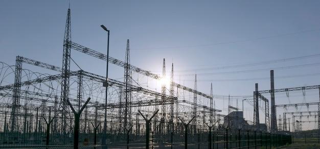 Paisagem industrial - diferentes estruturas de uma subestação elétrica em uma luz de fundo