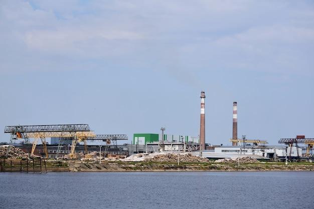 Paisagem industrial, fábrica de celulose e papel com pilhas de toras e chaminés à beira do rio