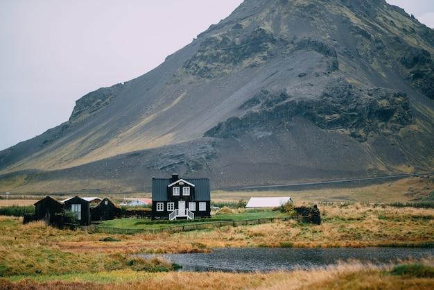Paisagem islandesa com uma casa contra altas montanhas