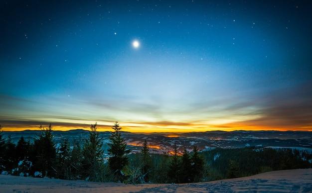 Paisagem mágica de floresta de coníferas crescendo entre as colinas no inverno contra um céu azul estrelado