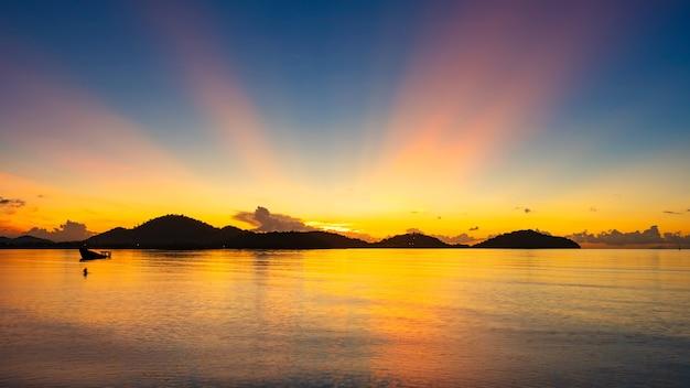 Paisagem majestosa do pôr do sol ou do nascer do sol luz incrível do céu da paisagem da natureza e nuvens se afastando, rolando nuvens coloridas do pôr do sol escuro com reflexo na superfície do mar da água