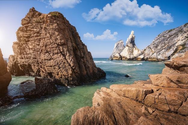 Paisagem marítima épica de penhascos elevando-se do oceano atlântico verde esmeralda. praia da ursa, sintra, portugal