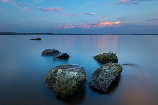 Paisagem meditativa com pedras de textura em primeiro plano e uma longa exposição com horizonte infinito