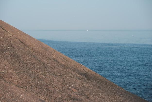 Paisagem minimalista. declive da rocha. mar ao fundo