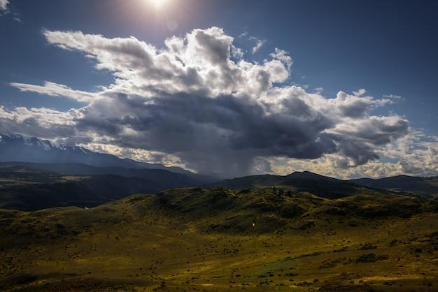 Paisagem misteriosa de montanha com colinas de nuvens de tempestade e raios de sol. céu bonito. a grama verde nas colinas brilha à luz do sol. foto com coloração. papel de parede para desktop ou smartphone.