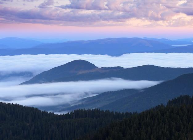 Paisagem montanhosa ao amanhecer. a manhã com lindas nuvens e nevoeiro