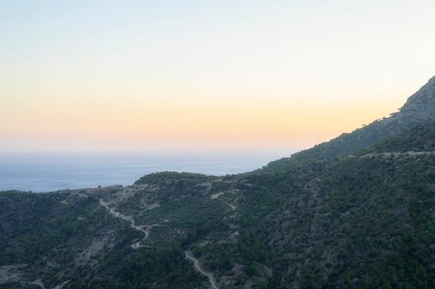 Paisagem montanhosa ao anoitecer com vista para o mar mediterrâneo