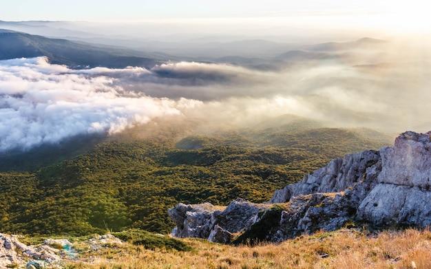 Paisagem montanhosa ao pôr do sol com nuvens baixas