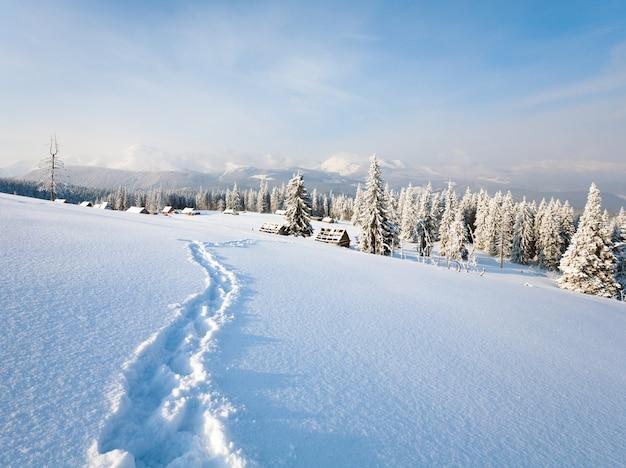 Paisagem montanhosa calma de inverno com grupo de galpões e cume do monte atrás (monte kukol, montanhas dos cárpatos, ucrânia)