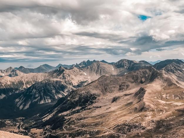 Paisagem montanhosa, colinas e cumes sob céu nublado