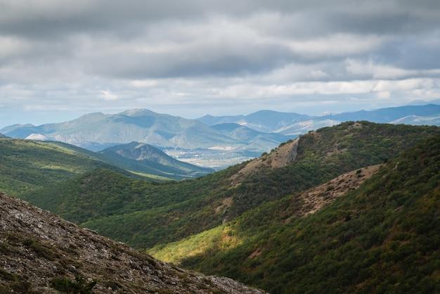 Paisagem montanhosa, colinas verdes em um dia ensolarado de verão, céu nublado