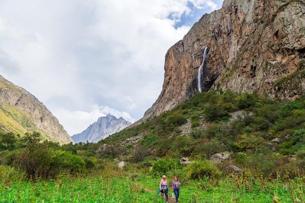 Paisagem montanhosa com cachoeira e turistas