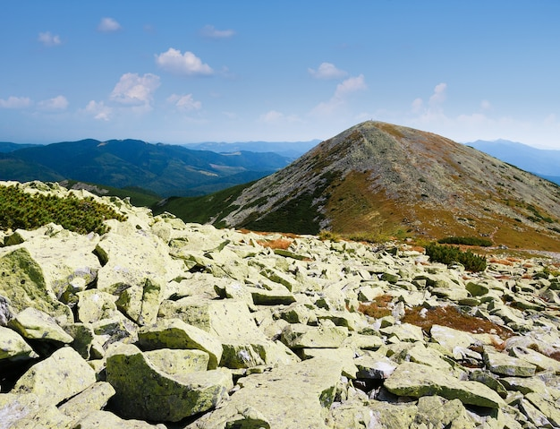Paisagem montanhosa com pedras na encosta. clima de verão ensolarado. vista no pico da montanha