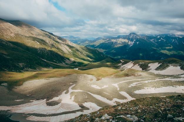 Paisagem montanhosa das montanhas com neve e céu sombrio principalmente nublado
