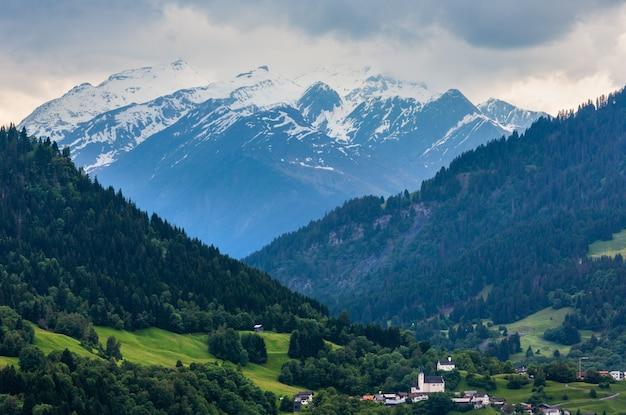 Paisagem montanhosa de alpes de verão com aldeia, floresta de abetos na encosta e topos rochosos cobertos de neve em longe, na áustria.