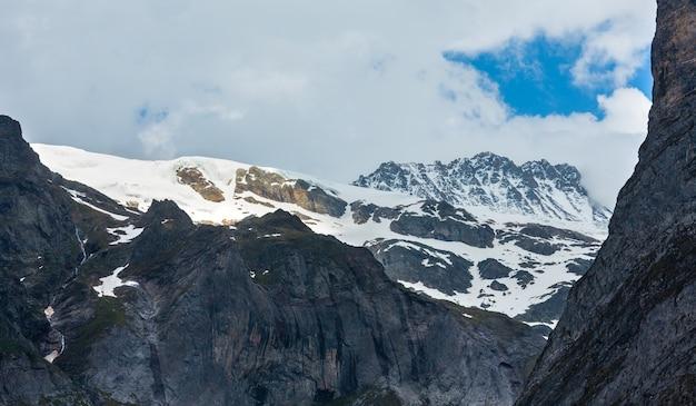 Paisagem montanhosa de alpes de verão com topos rochosos cobertos de neve em longe, na suíça.