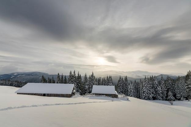 Paisagem montanhosa de inverno. casas de madeira antigas na clareira nevada no fundo do cume da montanha, floresta de abetos e céu nublado. cartão de feliz ano novo e feliz natal.