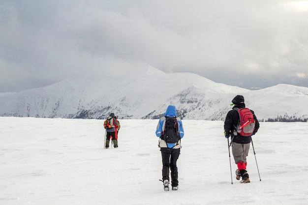 Paisagem montanhosa de inverno. três viajantes turistas caminhantes em roupas brilhantes com mochilas no campo nevado, caminhando em direção a uma montanha distante no fundo do espaço da cópia do céu nublado escuro azul tempestuoso.