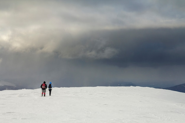 Paisagem montanhosa de inverno. vista traseira de viajantes turistas caminhantes com mochilas no campo nevado, caminhando em direção à montanha distante nublado céu azul escuro tempestuoso cópia espaço plano de fundo em um dia frio de inverno.