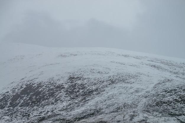 Paisagem montanhosa de nevoeiro com neve branca em rochas pretas em céu nublado. minimalismo de montanha enevoada do topo de uma montanha coberta de neve em nuvens baixas. fundo de natureza minimalista do pico da montanha de neve no nevoeiro.