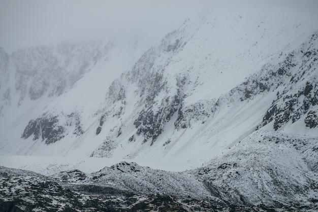 Paisagem montanhosa de nevoeiro com neve branca em rochas pretas em tempo nublado. minimalismo de montanha enevoada da montanha bloqueada pela neve em nuvens baixas. fundo de natureza minimalista da montanha nevada no nevoeiro.