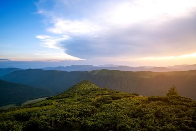 Paisagem montanhosa de noite de verão com colinas gramadas e picos distantes ao pôr do sol colorido.