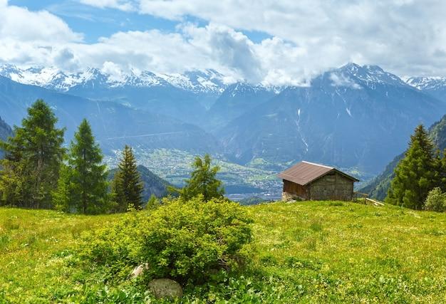 Paisagem montanhosa de verão com neve no topo do monte e casa na encosta (alpes, suíça)
