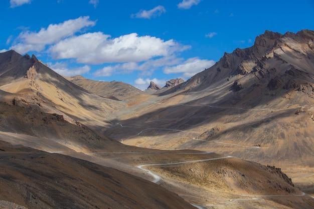Paisagem montanhosa do himalaia ao longo da rodovia leh para manali, na índia. estrada sinuosa e montanhas rochosas majestosas na região indiana do himalaia, ladakh, jammu e caxemira, índia. natureza e conceito de viagens