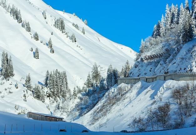 Paisagem montanhosa do inverno com abeto nevado e estrada na encosta (áustria, tirol).