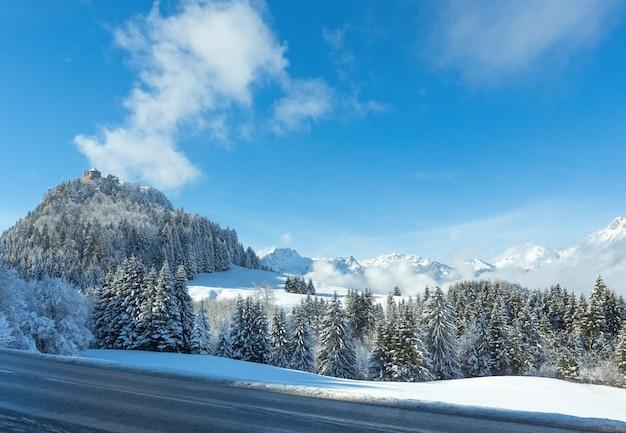 Paisagem montanhosa do inverno e o castelo de ehrenberg no topo da colina (áustria, baviera).
