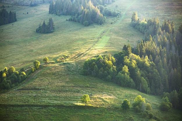 Paisagem montanhosa e prados iluminados pelo sol ao pôr do sol