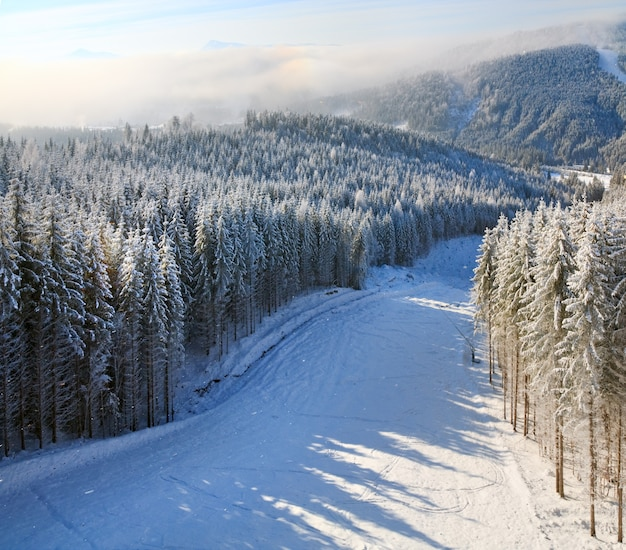 Paisagem montanhosa enevoada de inverno e neve com declive para esquiar