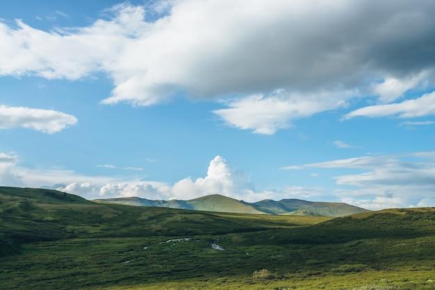 Paisagem montanhosa ensolarada verde com grande nuvem branca em forma de explosão no céu azul, acima das colinas verdes na luz solar. bela paisagem ensolarada com grande nuvem em forma de explosão acima de montanhas verdes.