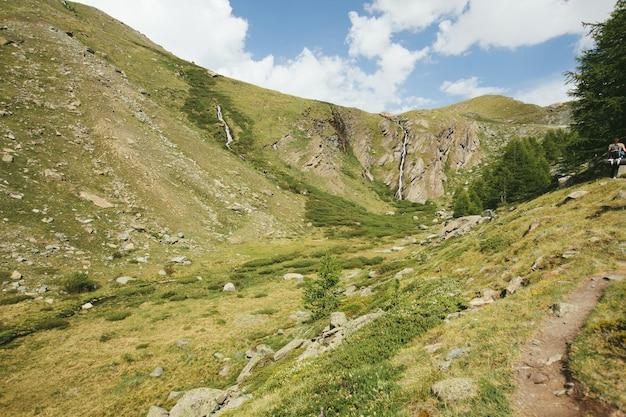 Paisagem montanhosa nos alpes com nuvens e cachoeiras
